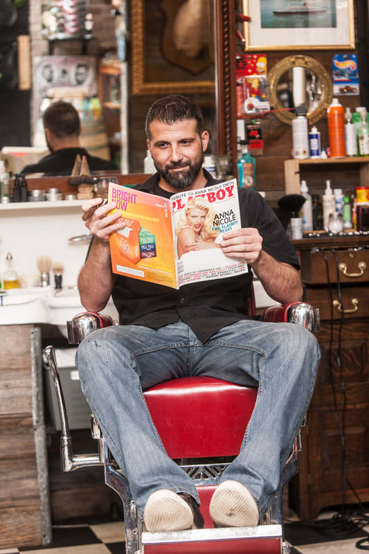 Rob from Back Alley Barber Shop on a barber chair reading a Playboy magazine